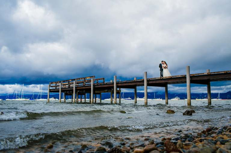 Bride and groom hugging on a Lake Tahoe pier.