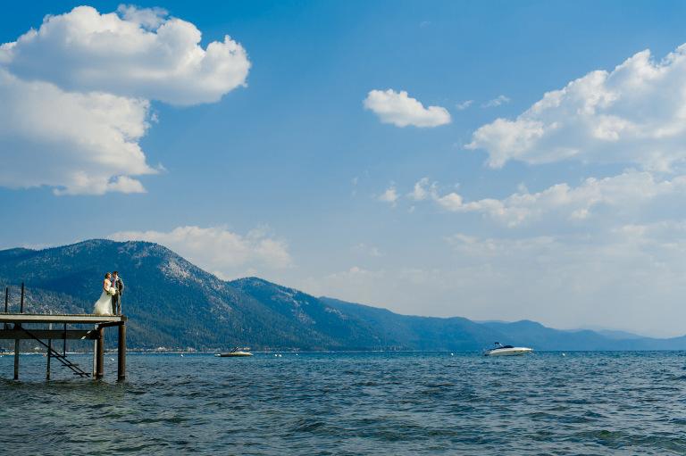 Wide angle Lake Tahoe wedding photo of bride and groom standing on the end of a pier.