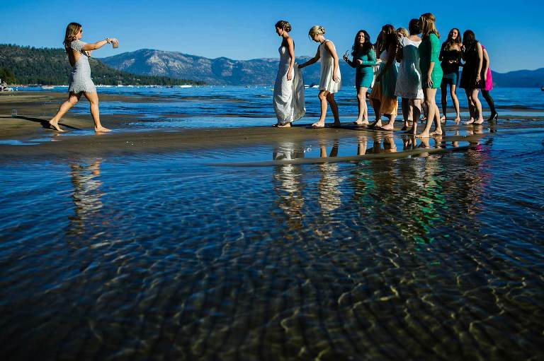 Bride and girlfriends walking on the beach in Lake Tahoe, CA.