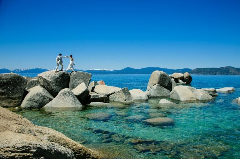 Sand Harbor wedding photo of bride and groom walking along the rocky shoreline.