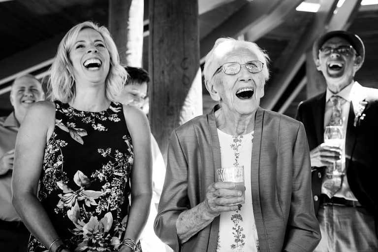 Black and white Sand Harbor wedding photo of bride's grandmother laughing.