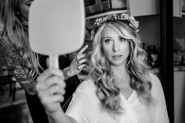 Blonde bride with a flower crown looking at herself in a handheld mirror.