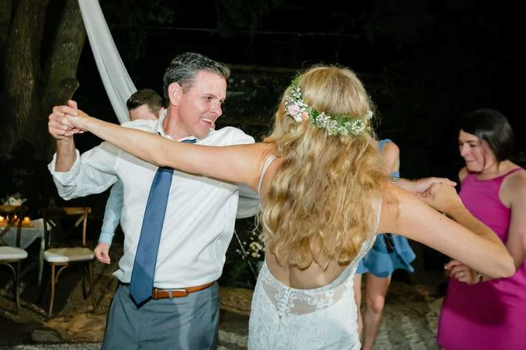 Bride and groom dancing together at a backyard wedding.
