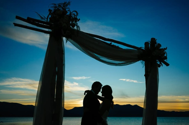 Bride and groom silhouetted at sunset in Lake Tahoe.