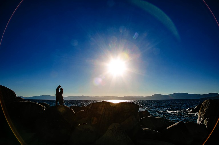 Dramatic engagement photo of silhouetted couple standing on rocks next to Lake Tahoe.