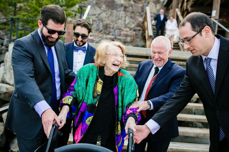 Grandmother of the groom in a colorful jacket being helped by groomsmen.