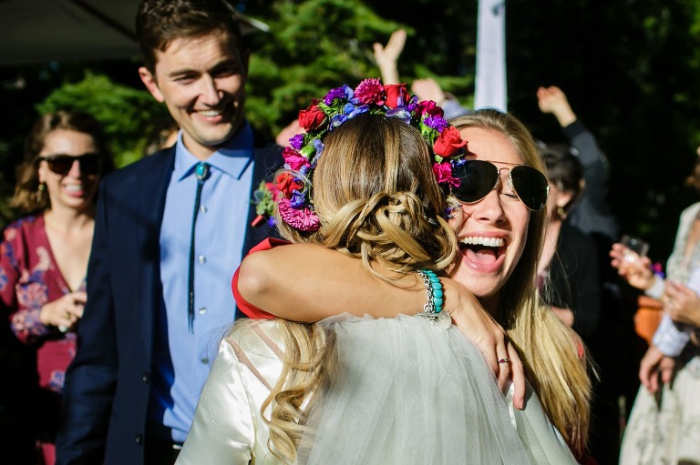 Lake Tahoe wedding reception photo of bride hugging her friend, whose sunglasses are getting bumped off.