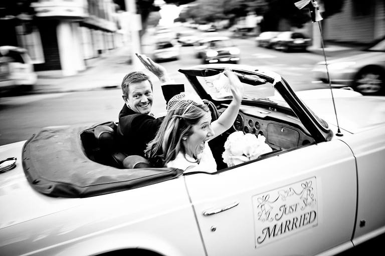 Bride and groom in their getaway car, leaving the reception on their way to their San Francisco wedding reception.