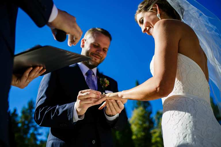 Groom putting on the bride's wedding ring during their outdoor Lake Tahoe wedding.