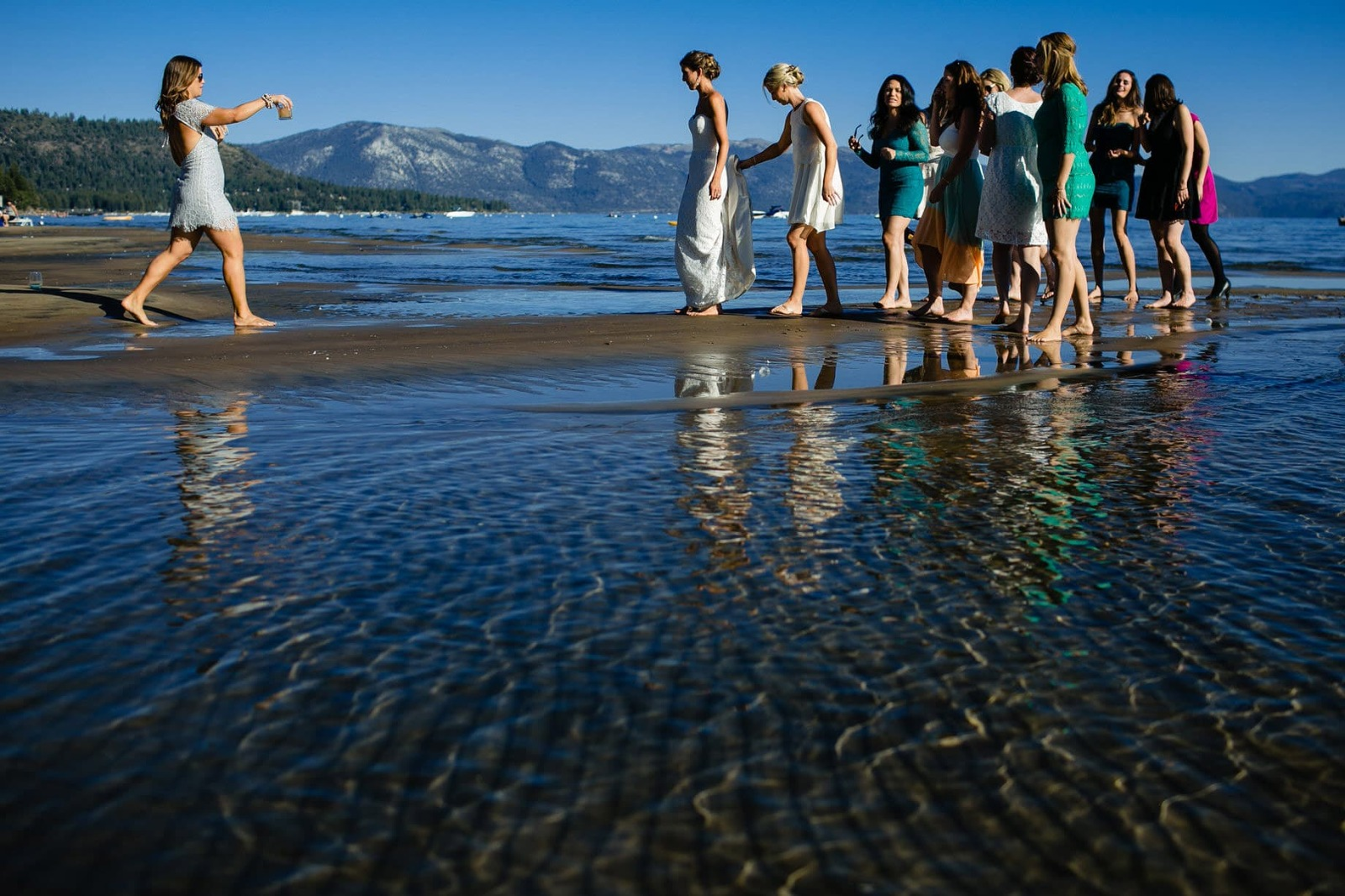 At a Lake Tahoe beach wedding, the bridesmaids' job is to take care of the bride and bring her whatever she needs!